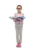 镜片阅读书的愉快的小女孩 免版税库存图片