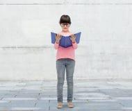 镜片阅读书的愉快的小女孩 库存图片