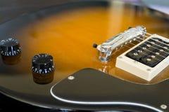 镶有钻石的旭日形首饰的金黄电吉他身体特写镜头  库存图片
