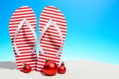 镶边啪嗒啪嗒的响声和圣诞节装饰站立在沙子的一个热带海滩反对与拷贝空间的晴朗的蓝天 免版税图库摄影