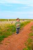 镶边夹克的孩子有花的在手上 免版税图库摄影