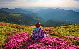 镶边格子花呢披肩的女孩坐草坪 免版税库存图片