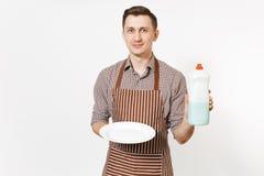 镶边棕色围裙的,衬衣人拿着白色回合空的板材,洗涤剂 与擦净剂液体的洗碗在瓶 图库摄影