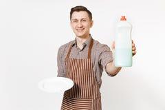 镶边棕色围裙的,衬衣人拿着白色回合空的板材,洗涤剂 与擦净剂液体的洗碗在瓶 免版税库存图片