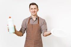 镶边棕色围裙的,衬衣人拿着白色回合空的板材,洗涤剂 与擦净剂液体的洗碗在瓶 库存图片