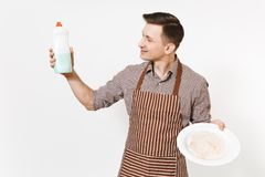 镶边棕色围裙的,衬衣人拿着白色回合肮脏的板材,洗涤剂 与擦净剂液体的洗碗在瓶 免版税图库摄影