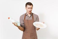 镶边棕色围裙的,衬衣人拿着白色回合肮脏的板材,洗涤剂 与擦净剂液体的洗碗在瓶 免版税库存照片