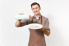 镶边棕色围裙的,衬衣人拿着白色回合肮脏的板材,洗涤剂 与擦净剂液体的洗碗在瓶 免版税库存图片