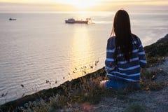 镶边毛线衣的无法认出的妇女敬佩在一座山的日落与海景 回到视图 免版税库存图片