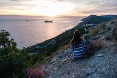 镶边毛线衣的无法认出的妇女敬佩在山的日落有海景视图侧视图 库存照片