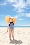 镶边泳装和大草帽的愉快的女孩在白色海滩 免版税库存图片