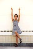 镶边礼服的愉快的年轻黑人妇女指向手指的  免版税库存图片