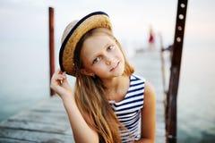 镶边背心和一个草帽的女孩反对海 免版税库存图片