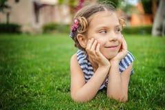 镶边背心的小女孩在绿色草坪说谎 库存图片