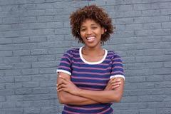 镶边衬衣的微笑的非洲妇女微笑对灰色墙壁的 库存照片