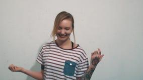 镶边衬衣的快乐的白肤金发的女孩有纹身花刺的笑在白色墙壁前面的 影视素材