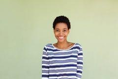 镶边衬衣的愉快的黑人妇女微笑由绿色背景的 免版税图库摄影