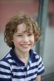 镶边衬衣的逗人喜爱的小男孩快乐地微笑着 免版税库存照片