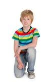 镶边衬衣的逗人喜爱的男孩坐 库存图片