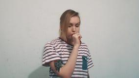 镶边衬衣的滑稽的白肤金发的女孩有纹身花刺的吹面颊在白色墙壁上 股票录像