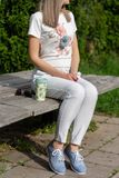 镶边裤子和蓝色鞋子的女孩坐一个长木凳在一杯咖啡和太阳镜旁边在晴朗的春天的公园 免版税图库摄影