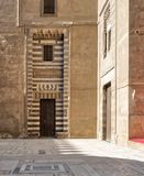 镶边黑白大理石装饰和石墙围拢的木年迈的门,开罗,埃及 图库摄影