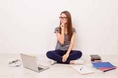镶边T恤杉和牛仔裤的si可爱的重视的女学生 免版税库存照片