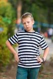 镶边T恤杉的男孩在公园 库存照片