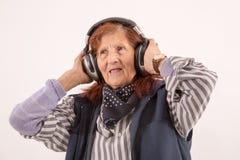 年长与耳机的夫人听的音乐 库存照片
