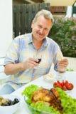 年长人吃在露台的午餐 免版税库存照片