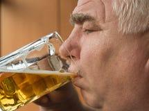年长人喝从玻璃杯子,特写镜头的啤酒 免版税库存照片