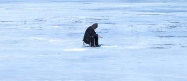 年长人在湖的冬天钓鱼 库存照片