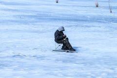 年长人在湖的冬天钓鱼 免版税库存照片