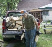 年长人帮助的堆木柴 免版税图库摄影