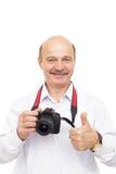 年长人拿着一台照相机并且显示赞许 库存图片