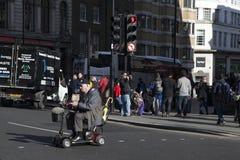 年长人推进流动性滑行车通过伦敦街道 免版税库存照片