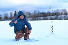 年长人渔在湖的冬天 免版税库存图片