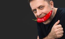 年长人用在他的嘴的红辣椒 免版税库存图片