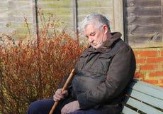 年长人睡着在阳光下。 免版税库存图片