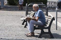 年长人读书报纸 图库摄影