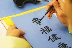 年长人画笔和贷方日本字符在蓝纸 图库摄影
