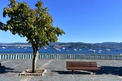 长凳、树和石扶手栏杆在海滩散步 在一个海湾的小船与大海,清楚的天空,好日子 加利西亚,西班牙 库存照片