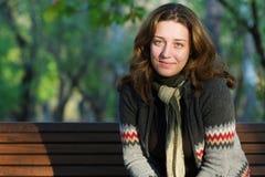 长凳公园俏丽的坐的妇女 免版税库存照片