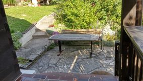 长凳和桌在老木房子附近 免版税库存图片