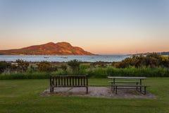 长凳和注视着到海和海岛的野餐桌日落 免版税库存图片