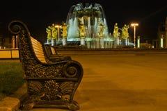 长凳和美丽的喷泉在晚上 免版税库存图片