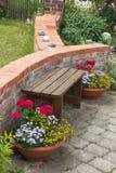 长凳和花在庭院里 免版税库存图片