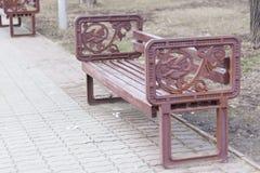 长凳在有葡萄酒扶手的公园 免版税库存照片