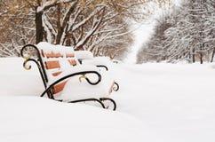 长凳在积雪的冬天公园 免版税库存图片