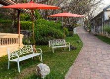 长凳在红色伞下在公园 库存照片